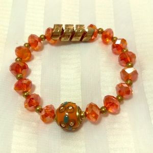 This orange beaded bracelet has engravings.